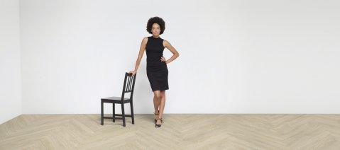 wineo 800 Designboden Verlegekombination hell Frau mit Stuhl