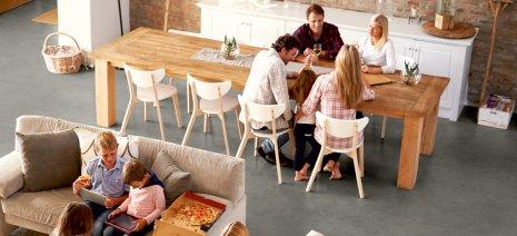 wineo Designboden mit Familie im Wohnbereich mit großem Tisch und Sofa