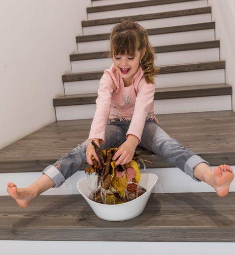 wineo Treppenkante Kind auf Treppe spielt mit Laub nass barfuß