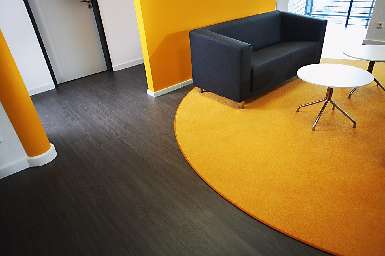 wineo Bodenbelag moderne Einrichtung dunkle holzoptik Sofa Tisch Teppich