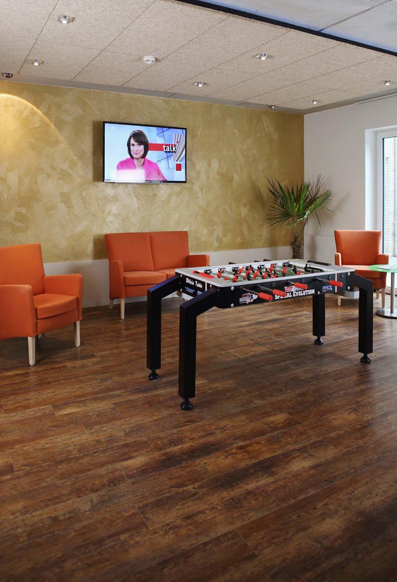 wineo Designboden im Seniorenheim Tischkicker Sofa Sessel Fußboden Vinyl Holzoptik