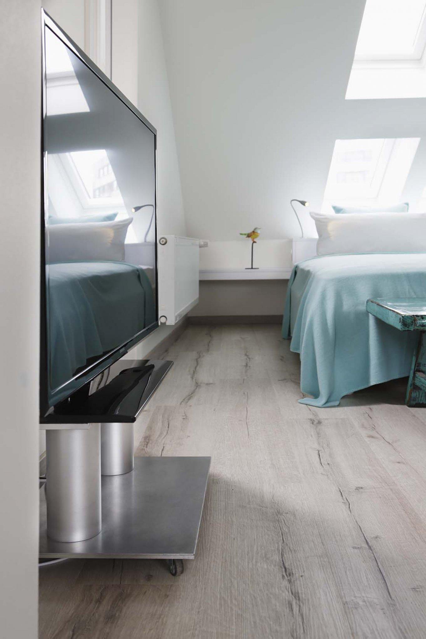wineo Purline Bioboden Holzoptik Planken Bett türkis Flachbildschirm Hotel