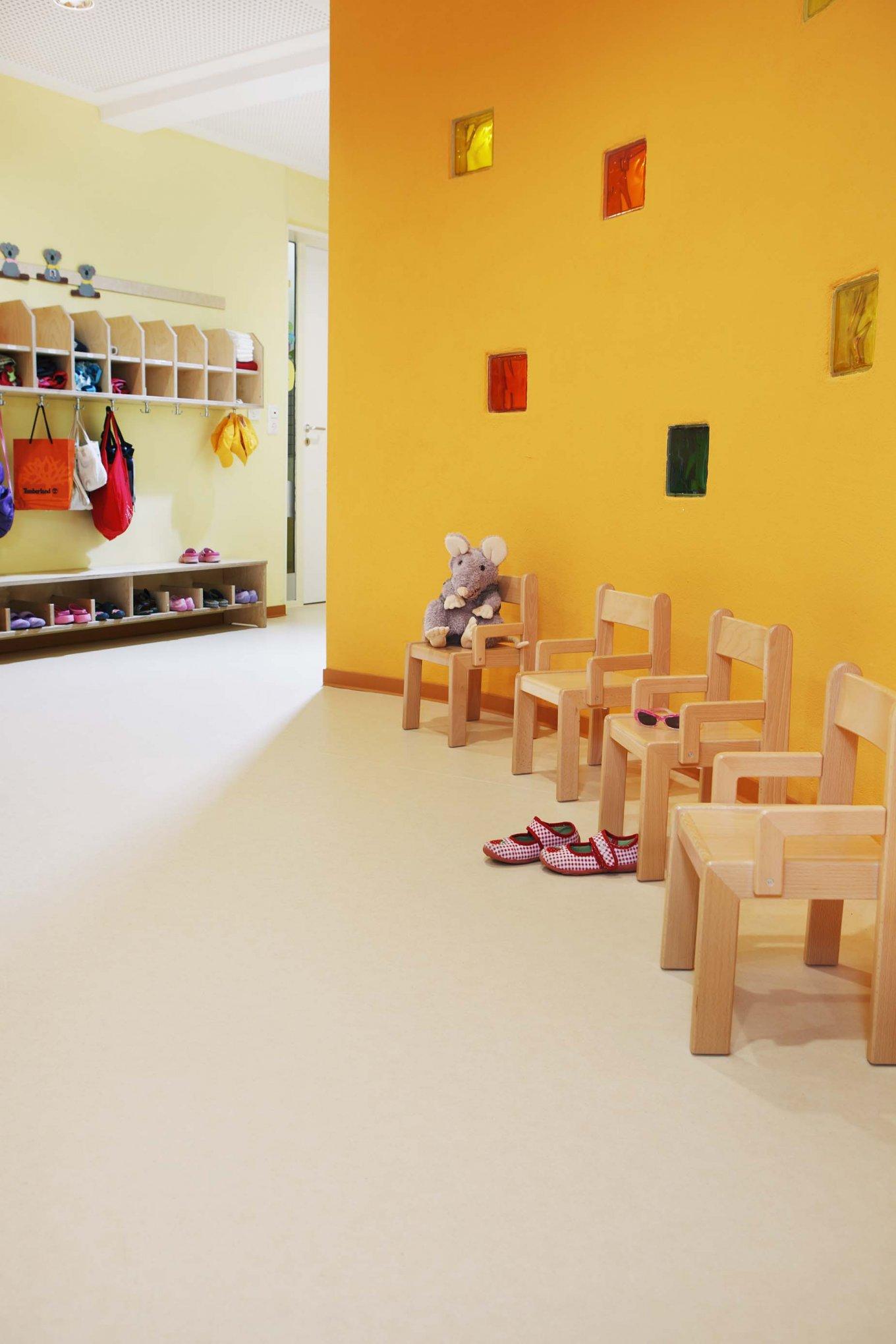 PURLINE Bioboden Sinai Sand in KiTa Kindergarten Eingangsbereich Stühle Rollenware Orange