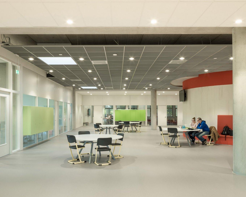 wineo Purline Bioboden Foyer groß hell Glasfenster Tische Stühle Farbaktzente